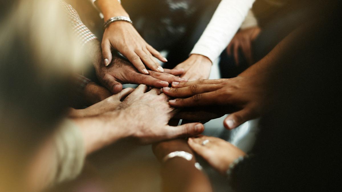 Team legt Hände in die Mitte